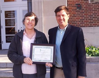 Nancy Holm and Bart Bartels of ISTC holding gold level certificate