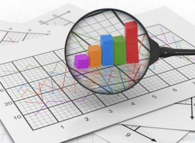 graphs and charts with a magnifying glass over the charts to look at metrics and data closer