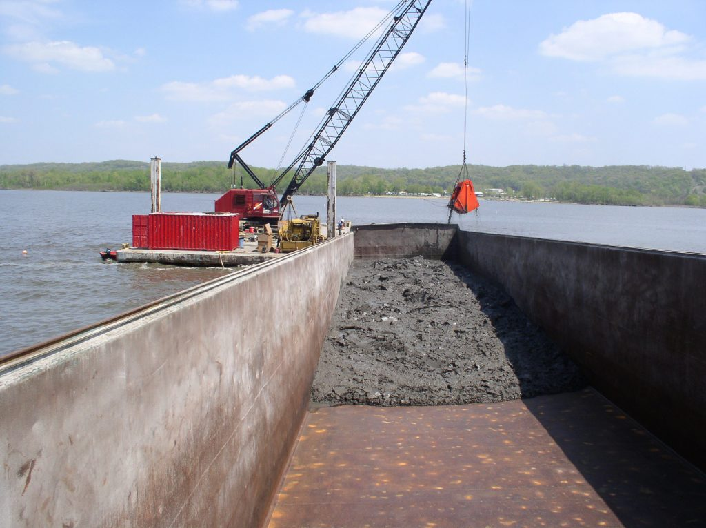 A crane removes sediment from Lower Peoria Lake during spring 2004. The dredging deepened a recreational boat channel at East Peoria. Care was taken to minimize water to reduce shipping costs. The barges traveled 165 miles to Chicago and were unloaded into trucks at the old US Steel South Works site.