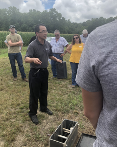 Wei Zheng demonstrates his bioreactor at Fulton County Field Day in July 2019.